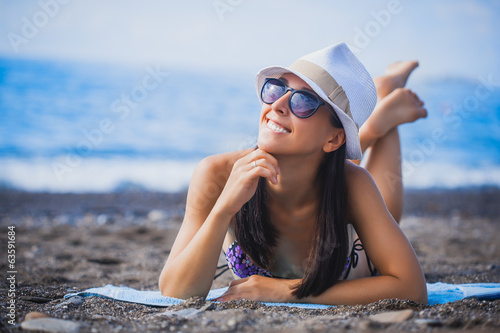 girl is lying on the beach with hat and swimsuit