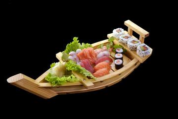 Sushi de salmón y atún en un barco de madera.