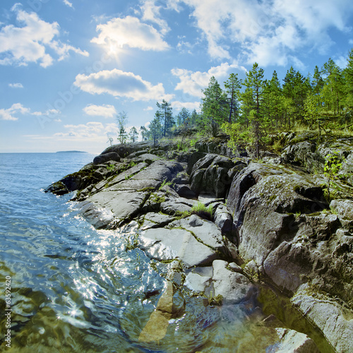 Sun and stony shore of Ladoga lake