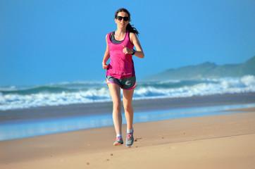 Woman running on beach, beautiful girl runner jogging outdoors