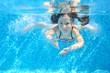 Leinwanddruck Bild - Happy active underwater child swims in pool, girl swimming