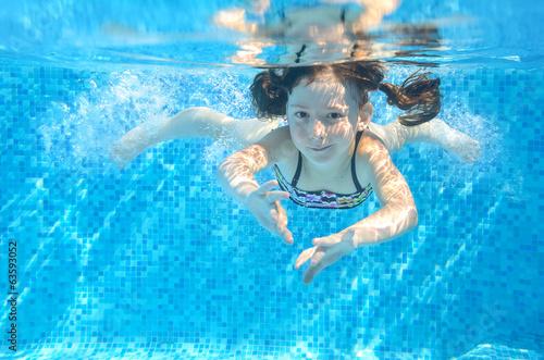 Leinwandbild Motiv Happy active underwater child swims in pool, girl swimming