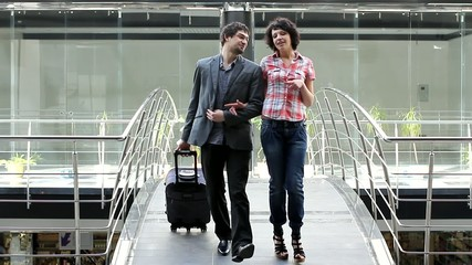 A man and a woman are going over the bridge with suitcase (PAL)