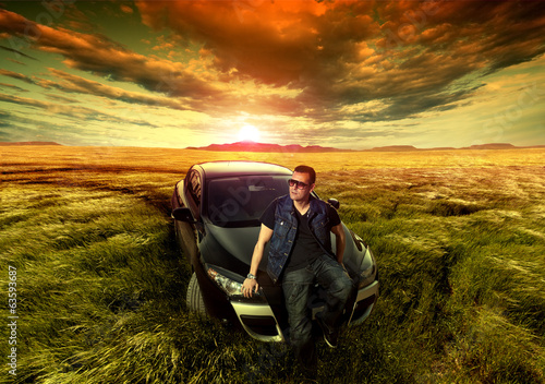 Dreamy fields sunset landscape and fashion man with a car