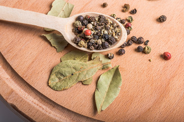 spoon with spices and  bay leaves on wooden board
