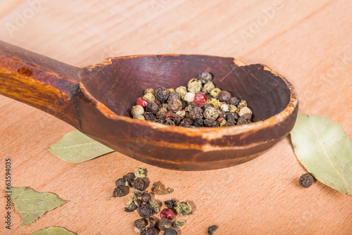 old-fashioned wood spoon with spices and  bay leaves
