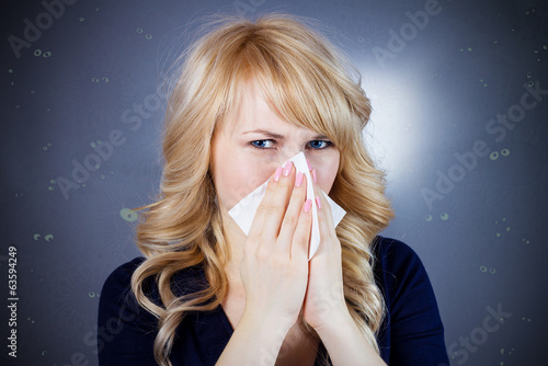 Woman with cold, germs, blowing her nose