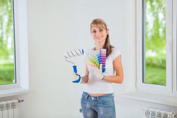 smiling female holding paintroller and color palette at home