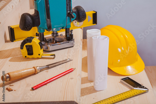 set of carpenter tools on steps of wooden ladder