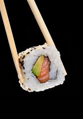 Sujetando sushi roll de salmón en fondo negro.