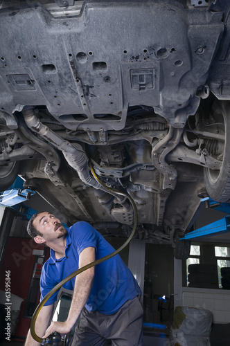 Mechanic draining engine oil at auto repair shop for oil change