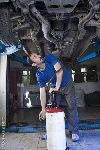 Mechanic Draining Oil