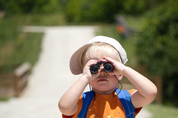 Little boy searching, searches with binoculars