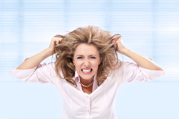 Angry woman pulling her hair in frustration.