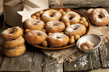 Ceramic plate of sugar donuts  on wooden table