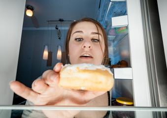 portrait of woman taking donut from fridge