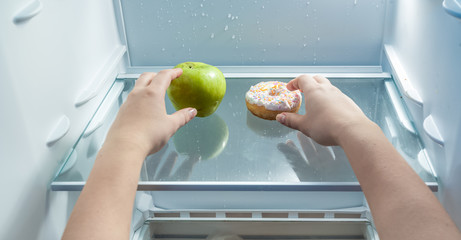 hands taking green apple and donut from fridge
