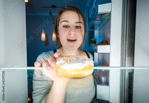 young woman taking donut out of fridge at night