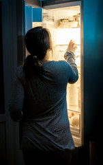 hungry woman looking in fridge at late night