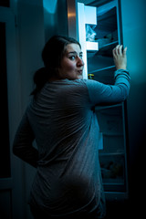 Shot at night of woman opening refrigerator