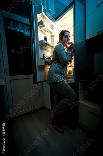 hungry woman eating at night near refrigerator