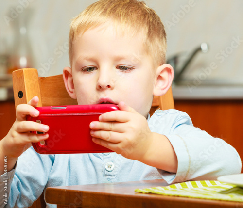 Happy childhood. Blond boy kid child playing with mobile phone