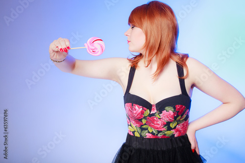 Sexy woman holding candy. Redhair girl eating sweet lollipop