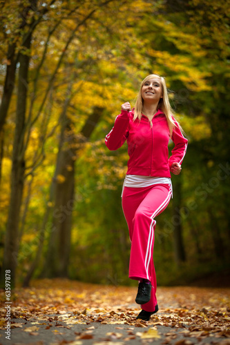 Fitness woman girl doing exercise in autumnal park. Sport.