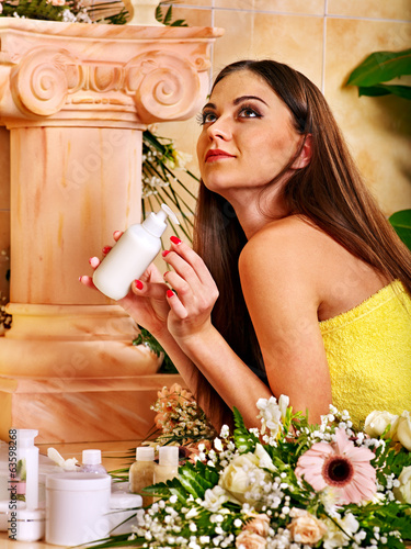 Woman applying moisturizer.