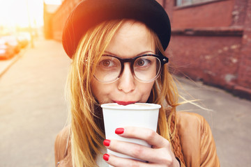 stylish woman in glasses drinking coffee in morning sunshine