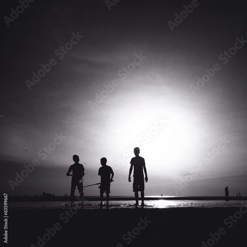 silhouette of three male friends walking on the beach