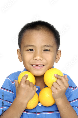 Boy holding oranges isolated on white background