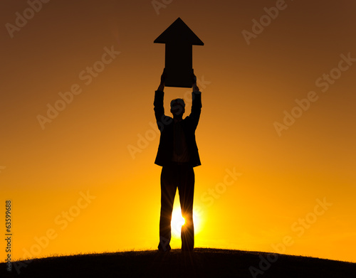 Silhouette of Businessman Holding Arrow Sign
