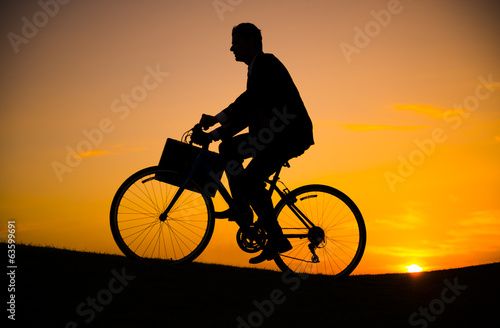 Businessman riding bicycle on the hill