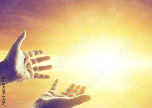 Hands in bright sky