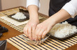 Woman chef wetting fingers to close sushi rolls