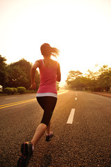 young fitness woman running at sunrise driveway