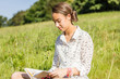 Beautiful young student reading a book in the park