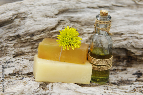 daisy flower on soap and massage oil on rustic wood texture