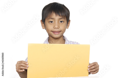 A laughing boy is holding a sheet of red paper