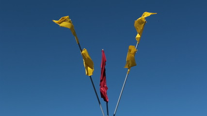 Red and yellow flags waving on the flagpoles against blue sky