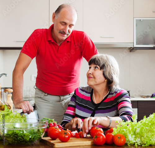 senior man and mature woman cooking   in  kitchen