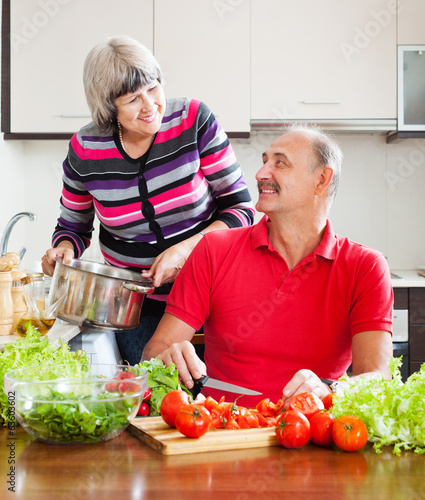 loving mature couple cooking  in kitchen