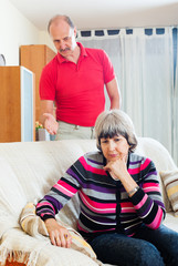 Tired mature woman listening to angry husband
