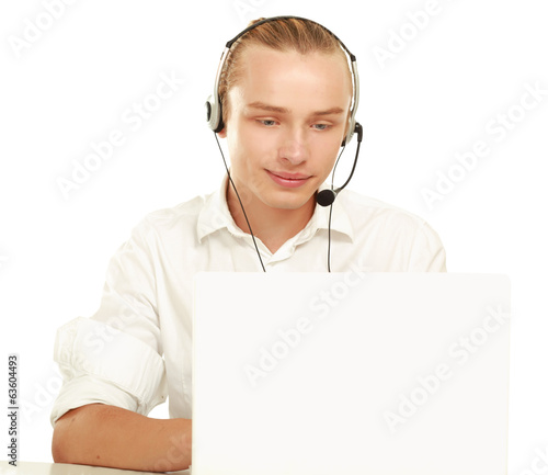 A young businessman with a headset in front of a laptopю