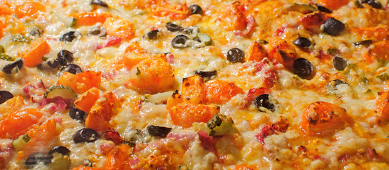 Close-up of pizza with tomato, cheese and olives.