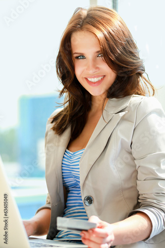 Young woman sitting with laptop and credit card in her hand.