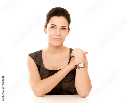 A young woman sitting at the desk, isolated on white background.