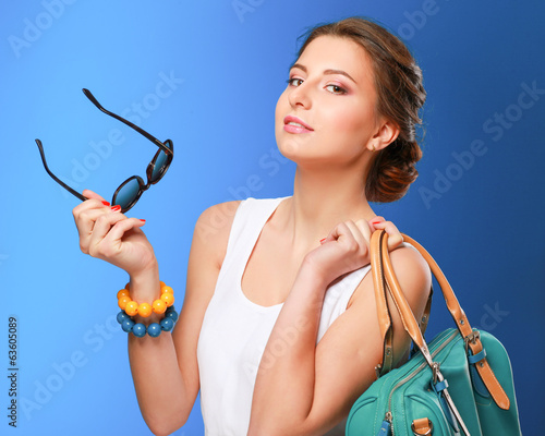 The fashionable young woman in sunglasses holding bag.