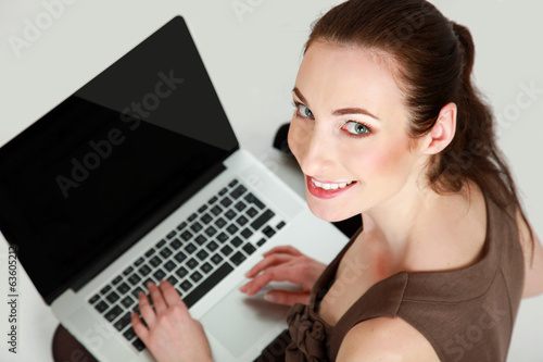 Businesswoman with laptop sitting on the floor